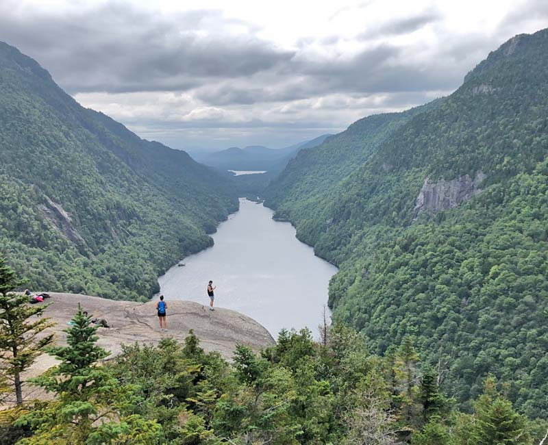 Hikers on a large rock overlooking a lake and the Adirondack Mountains